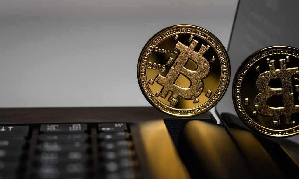 Bitcoin coin on laptop screen and keyboard