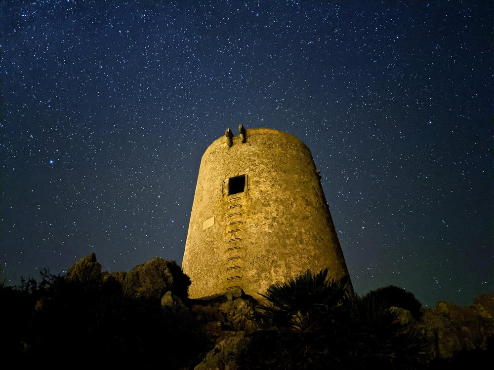 a stone tower at night with a starry sky in the background