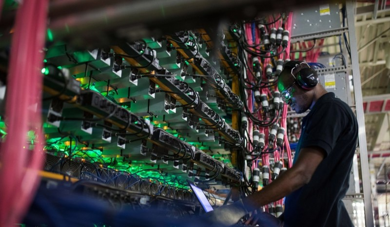 A technician monitors cryptocurrency mining rigs at a Bitfarms facility in Saint-Hyacinthe, Quebec, Canada, in July 2018. Photo: Bloomberg